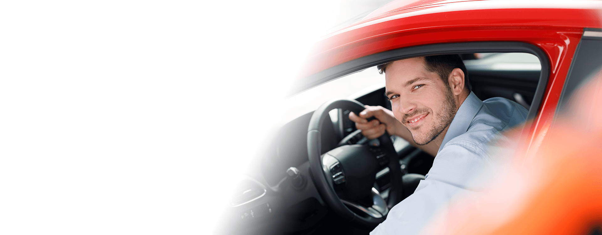 man smiling sitting in the car with doors opened